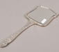 A silver hand mirror with machine tur...