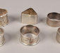 Six silver serviette rings, including...