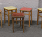 Five wooden stools four with vinyl se...