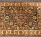 An Indian green ground wool rug with ...