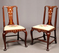 A pair of George I walnut hall chairs of