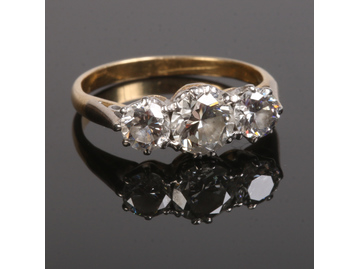 A gold three stone diamond ring set with